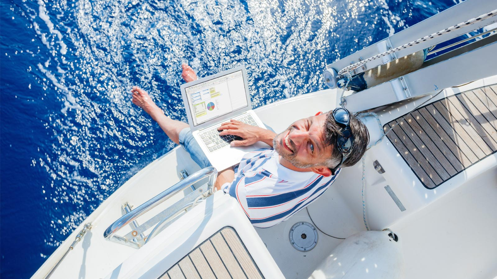 Man with laptop aboard a sailing yacht
